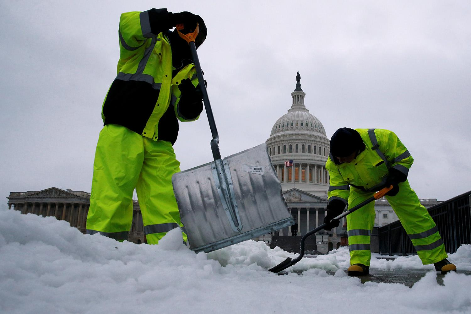 <p>Workers clear snow from a walkway on Capitol Hill during a winter storm in Washington, March 14, 2017. (Jonathan Ernst/Reuters) </p>