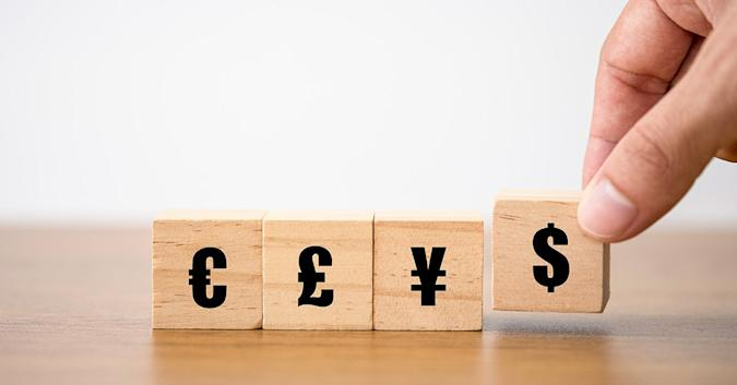 Stock image showing currency symbols printed on wooden tiles similar to Scrabble tiles.