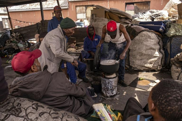 A group of reclaimers -- people who pick up and sell recyclable rubbish -- cook food at the Bekezela slum in Johannesburg. Most people here are depending on food donations to survive during the country's lockdown (AFP Photo/Emmanuel Croset)