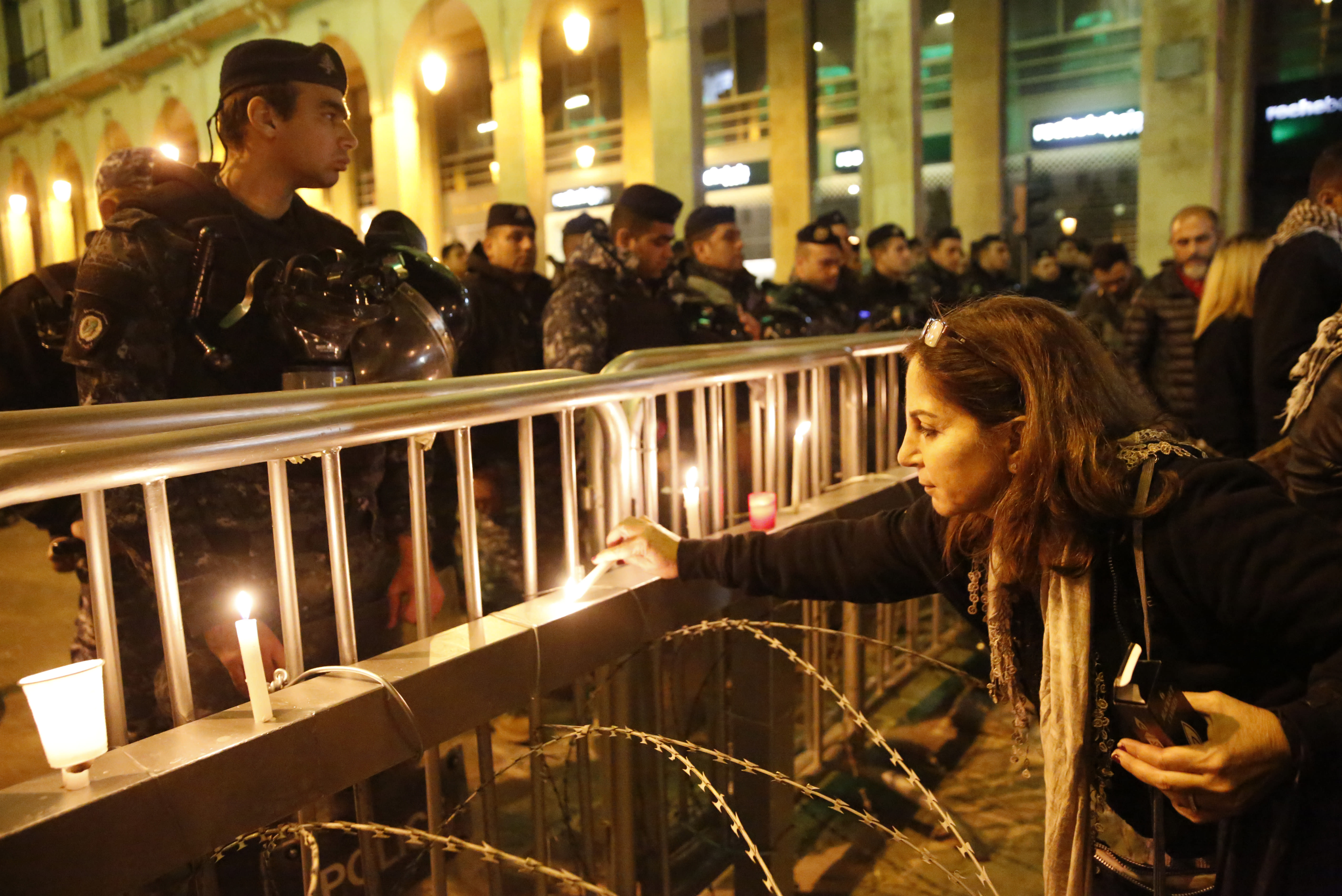 An anti-government protester lights a candle in front the riot police, during ongoing protests against the ruling elite of corruption and financial crisis, in downtown Beirut, Lebanon, Wednesday, Dec. 18, 2019. Lebanon's caretaker prime minister said Wednesday he's no longer a candidate for the post, eliminating himself from consideration on the eve of scheduled consultations between the president and parliamentary blocs for naming a new premier. (AP Photo/Hussein Malla)