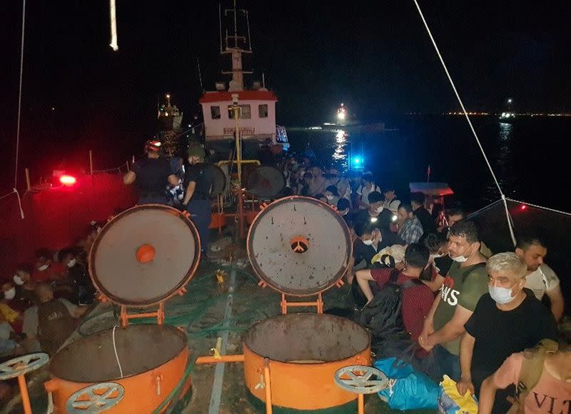 Members of Turkish Coast Guard Command stand guard next to migrants on the deck of a cargo ship during a raid in Izmir