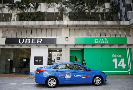 A ComfortDelgro taxi passes Uber and Grab offices in Singapore March 26, 2018. REUTERS/Edgar Su