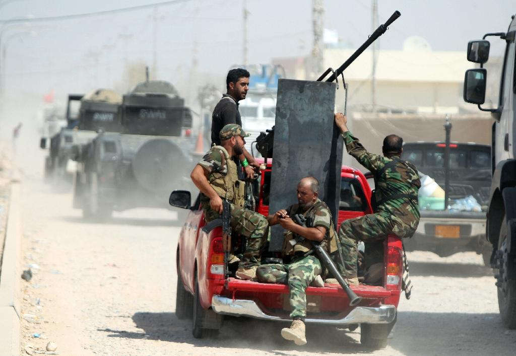 Iraqi Shiite militia fighters ride in a truck after pushing back Islamic State group militants on September 3, 2014, on the road between Amerli and Tikrit