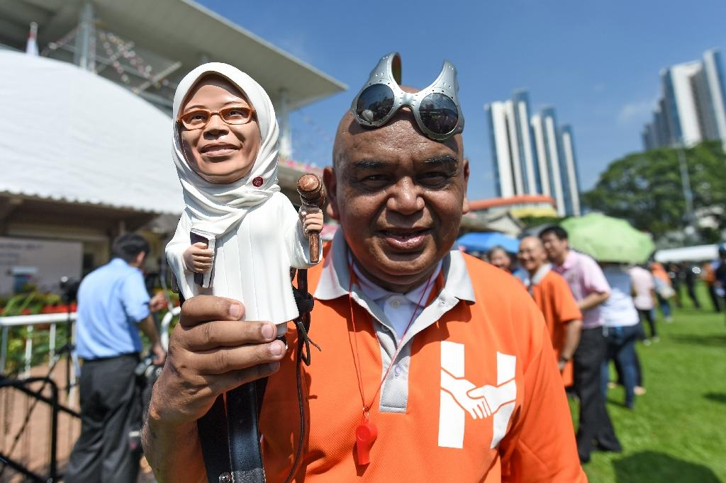 A supporter displays a figurine of former parliamentary speaker Halimah Yacob, who has been named the country's new president (AFP Photo/ROSLAN RAHMAN)