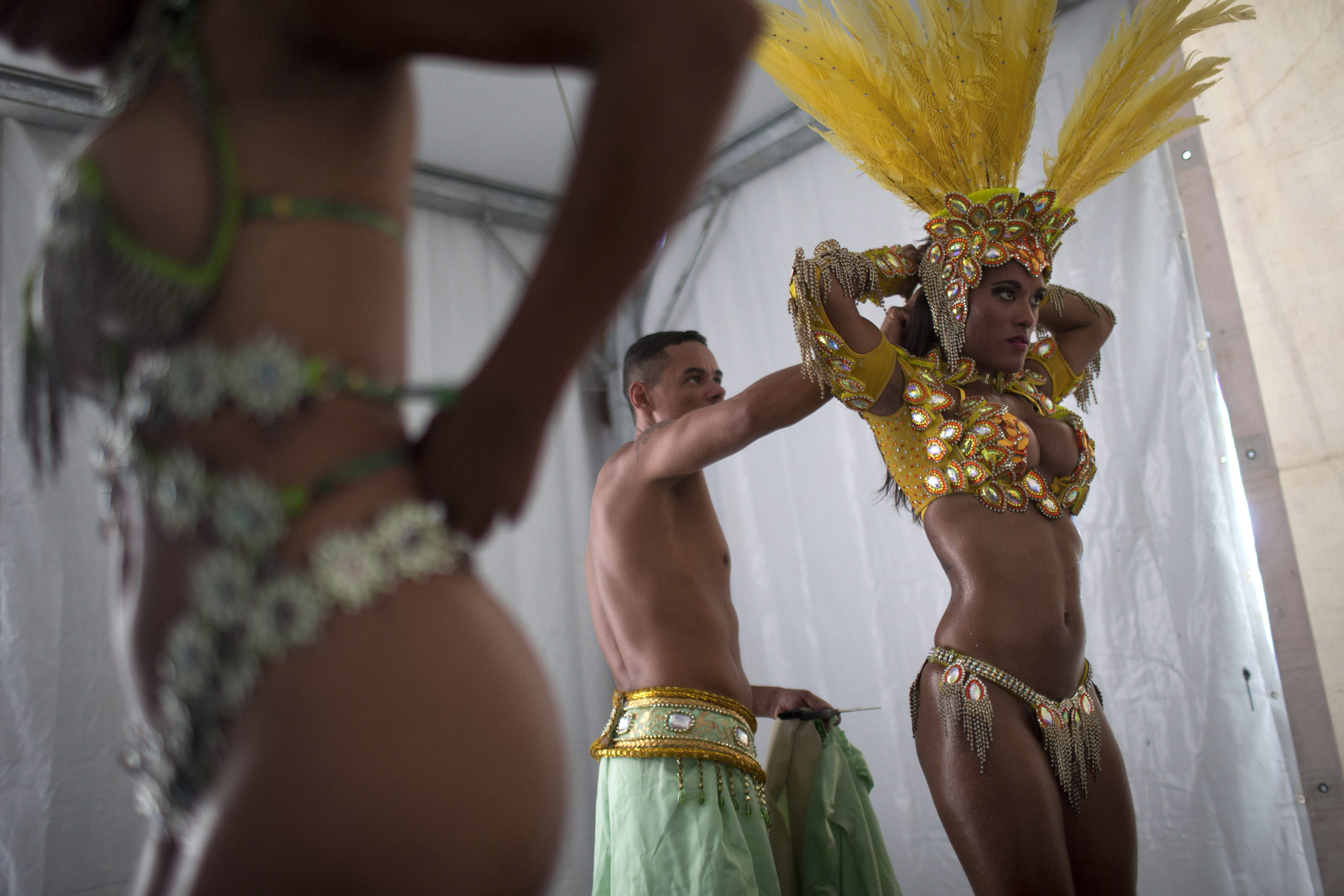 """In this photo taken Saturday, Feb. 2, 2013, samba dancer Diana Prado, right, is with her costume as she prepares for a carnival parade at central station in Rio de Janeiro, Brazil. Though samba dancers, or """"passistas,"""" as they're known in Portuguese, are unquestionably the star attractions of the world's most iconic Carnival celebrations, they're not on the payroll of the samba school they represent. (AP Photo/Felipe Dana)"""
