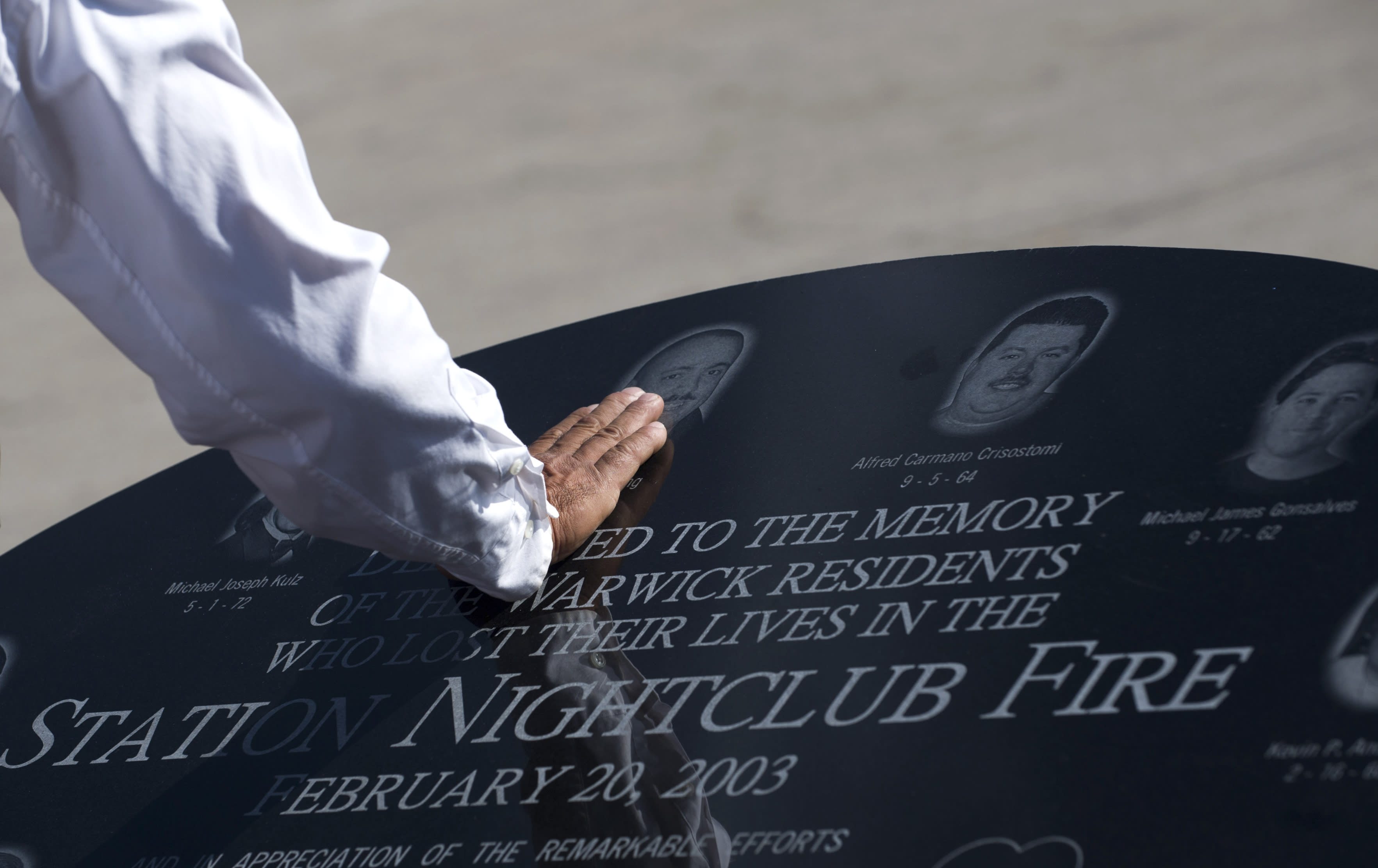 Jody King, of Warwick, R.I., touches the image of his brother Tracy King, following a ceremony, in Warwick, Saturday, Oct. 20, 2012, held to unveil a memorial stone that honors victims of the 2003 Station Nightclub Fire, in West Warwick, R.I. The Warwick memorial places a special focus on the 10 Warwick residents who died in the Feb. 20, 2003, fire at The Station nightclub, which happened when pyrotechnics for the rock band Great White ignited flammable foam that lined the walls of the club. Nine of the Warwick residents' names are inscribed in a granite slab that sits at the top of a 28-foot-diameter brick circular plaza. Around the exterior of the circle are 100 8-by-8-inch bricks inscribed with the name of every person who died. (AP Photo/Gretchen Ertl)