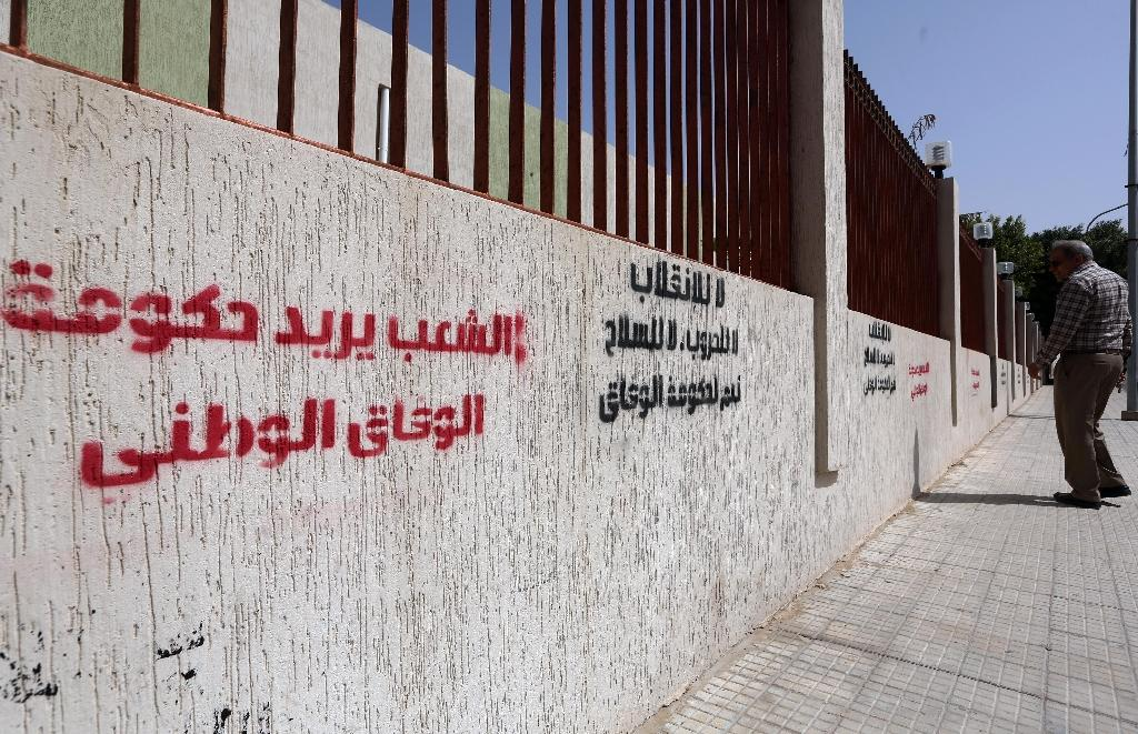 """A man walks past graffiti in Arabic: """"The people want the Government of National Accord"""" (L) and """"No to the coup, no to wars, no to weapons, yes for the Government of National Accord"""" (C), on April 4, 2016, in the Libyan capital Tripoli (AFP Photo/Mahmud Turkia)"""