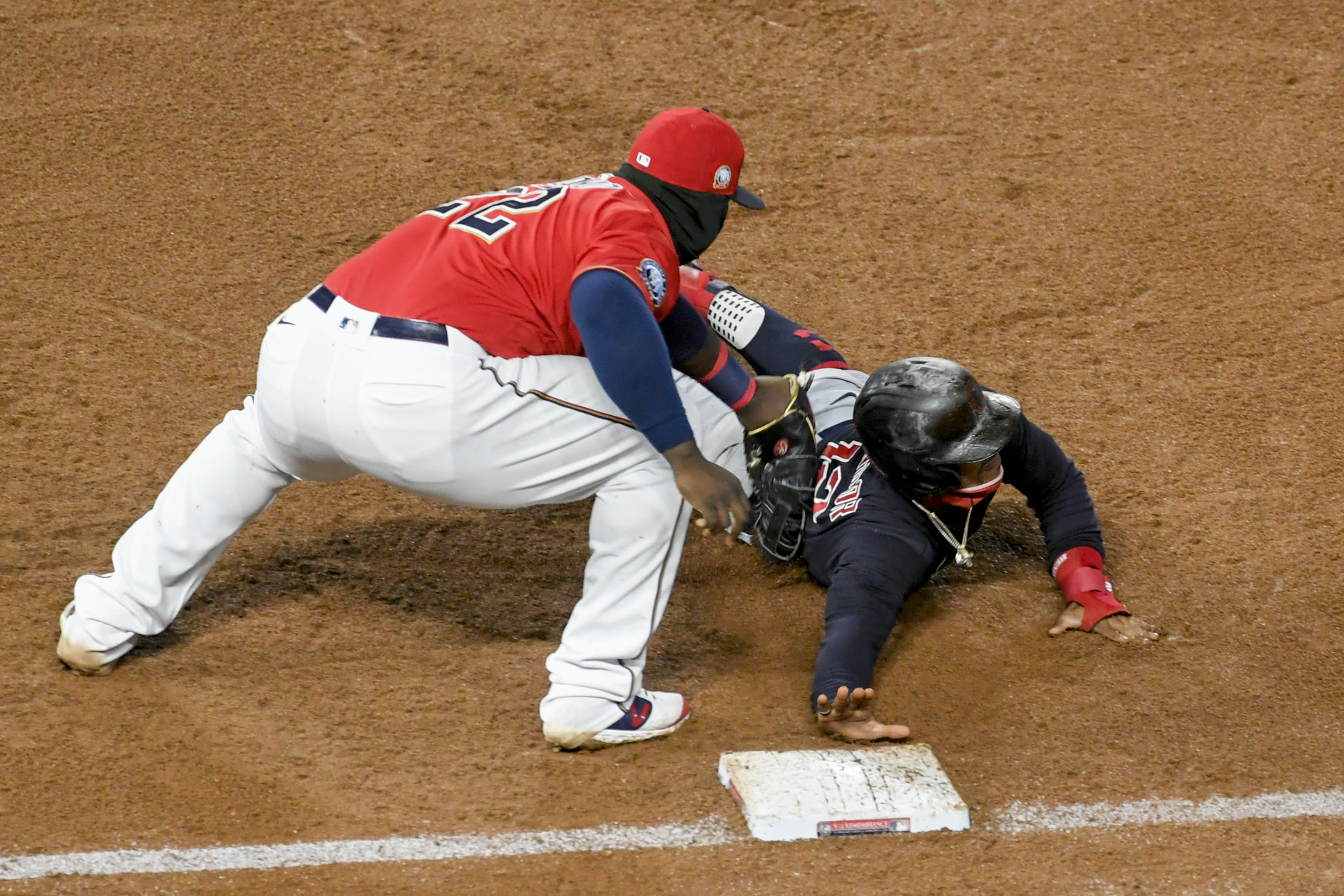 Minnesota Twins first baseman Miguel Sano picks off Cleveland Indians Francisco Lindor as Lindor dives back to first during the sixth inning of a baseball game Friday, Sept. 11, 2020, in Minneapolis. (AP Photo/Craig Lassig)
