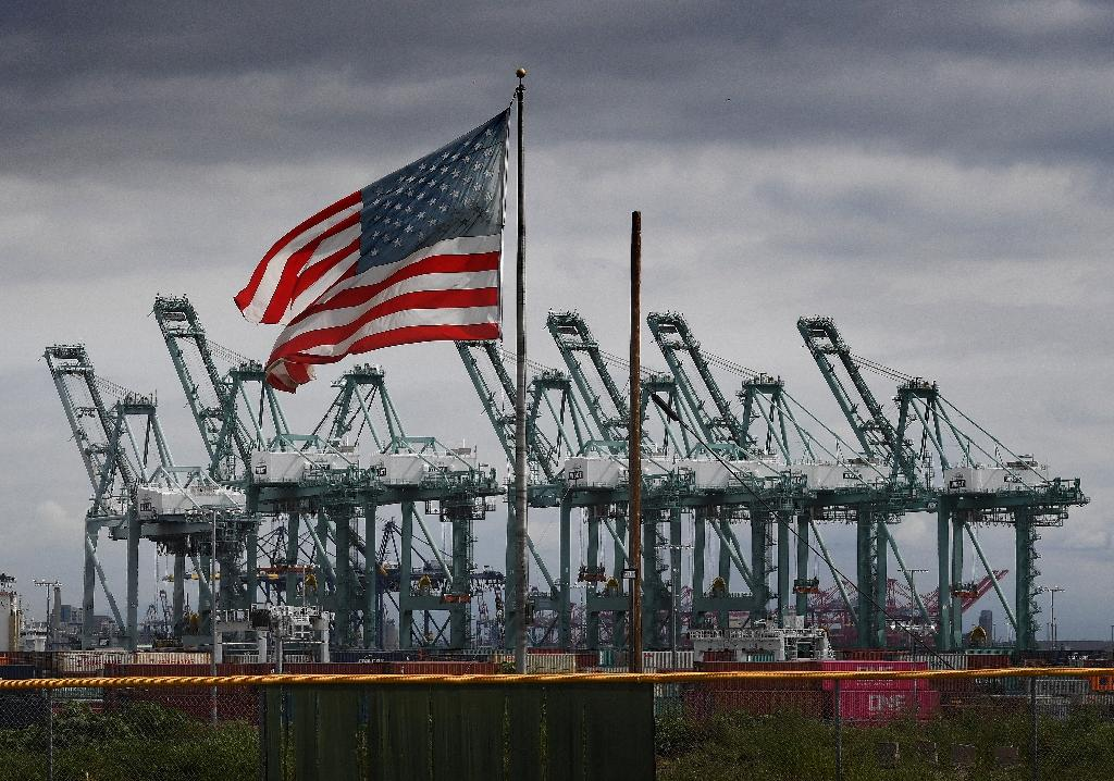 The US flag flies over shipping cranes and containers in Long Beach, California, as manufacturers express concerns including over higher costs due to tariffs, the Federal Reserve said (AFP Photo/Mark RALSTON)