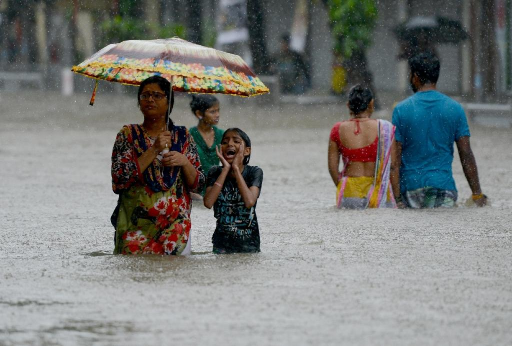 Indian people are seen wading through a flooded street last month during heavy rain showers in Mumbai (AFP Photo/PUNIT PARANJPE )