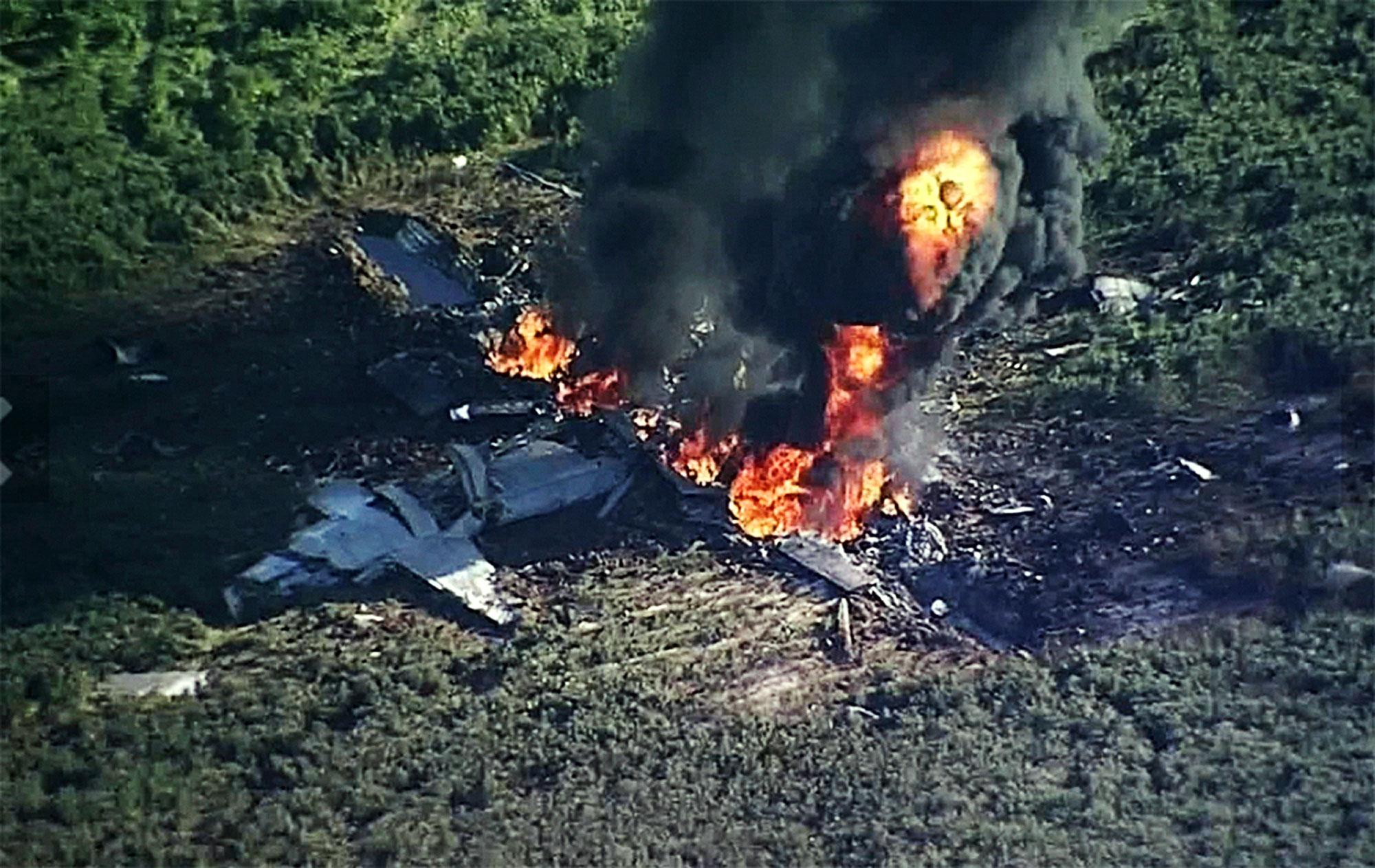 <p>In this Monday, July 10, 2017 frame from video, smoke and flames rise from a military plane that crashed in a farm field, in Itta Bena, Miss. (Photo: WLBT-TV via AP) </p>