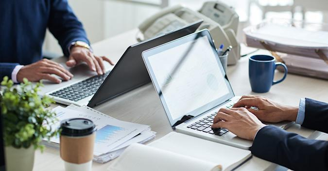 Stock image of two people sitting across from each other, typing on laptops.