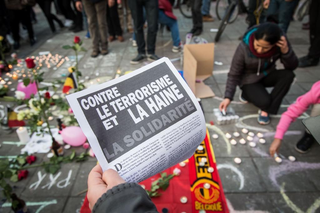 A man holds a flyer reading 'Against terrorism and hate' at a makeshift memorial in front of the stock exchange at the Place de la Bourse in Brussels on March 22, 2016, following triple bomb attacks in the Belgian capital (AFP Photo/Aurore Belot)