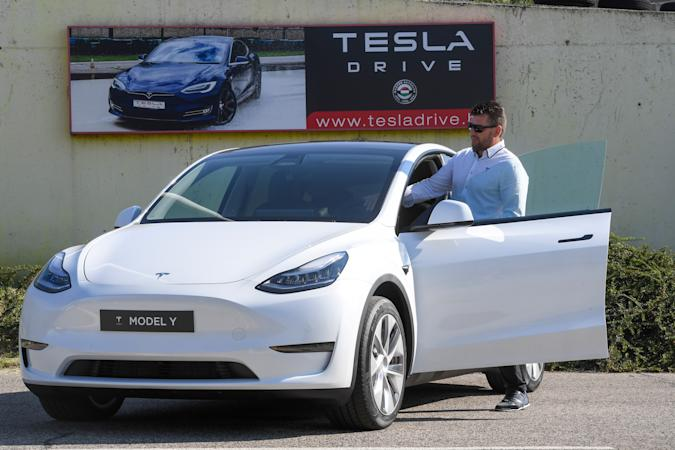 """A picture taken on September 5, 2020 shows a driver testing a """"Tesla Model Y"""" car, an all-electric compact SUV by US electric car giant Tesla, during its presentation at the Automobile Club in Budapest. (Photo by ATTILA KISBENEDEK / AFP) (Photo by ATTILA KISBENEDEK/AFP via Getty Images)"""