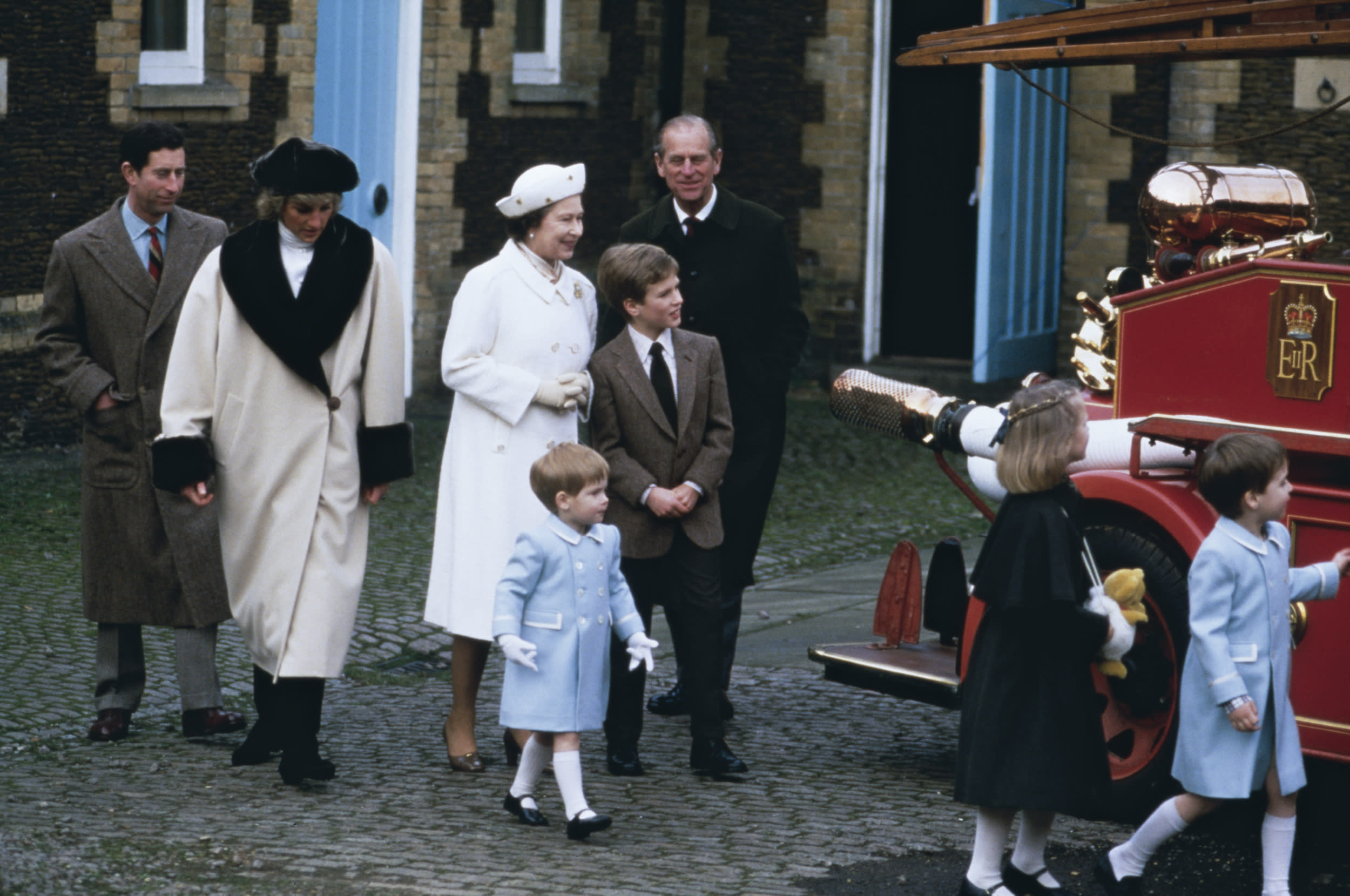 A royal family visit to a museum in Sandringham, where the children climb on a fire engine, January 1988. From left to right Prince Charles, Princess Diana, Queen Elizabeth, Peter Philips, Prince Philip, Duke of Edinburgh, Prince Harry, wearing a blue coat, Zara Phillips and Prince William.  (Photo by Jayne Fincher/Princess Diana Archive/Getty Images)