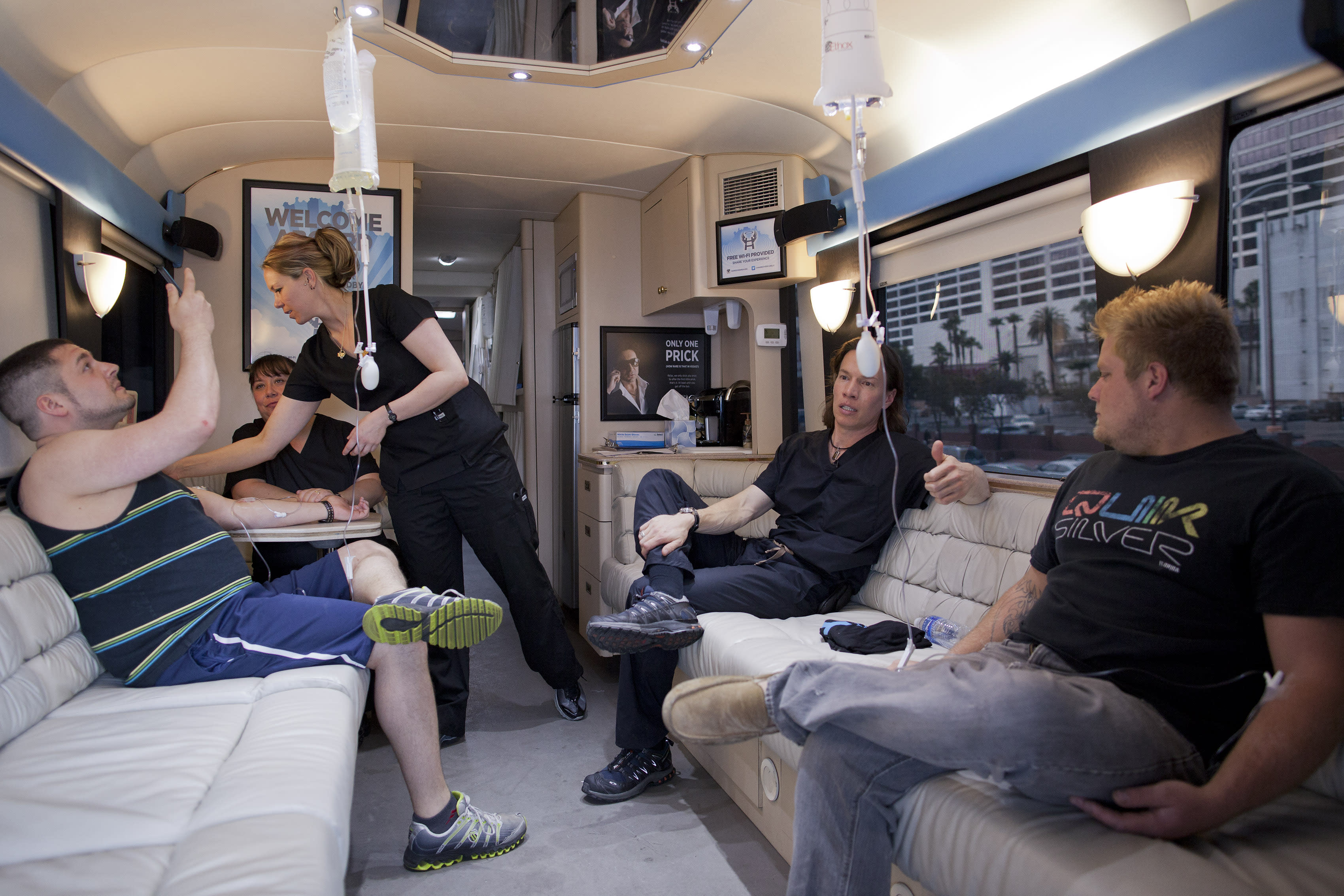 Bryan Dalia, left, of Caldwell, N.J. makes a photo of his IV bag while being treated on the Hangover Heaven bus by EMT Stacey Kreitlow, second from left, and Dr. Jason Burke, second from right, as another patient named Alex, right, looks on, Saturday, April 14, 2012, in Las Vegas. The bus picked up 16 patients on its first weekend as a mobile treatment center for tourists who spent the night before drinking in all the nightlife Las Vegas has to offer. For a fee, they get a quick morning-after way to rehydrate, rejuvenate and resume their revelry. (AP Photo/Julie Jacobson)