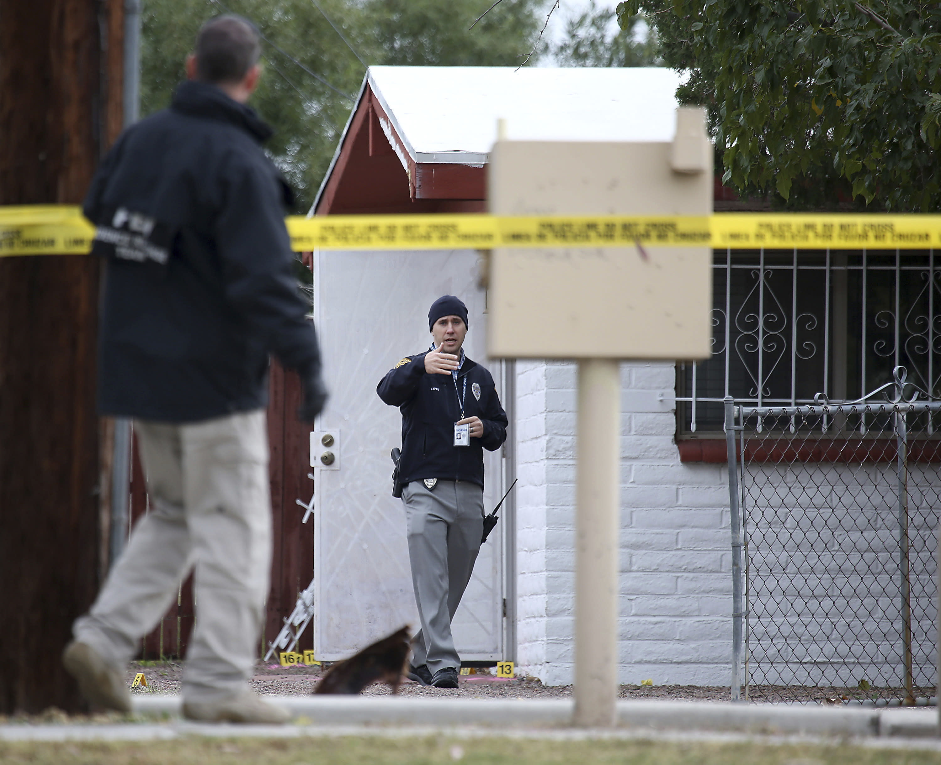 Law enforcement personnel continue their investigation at the scene following a shooting Friday, Nov. 30, 2018, in Tucson, Ariz. A deputy U.S. marshal serving a felony arrest warrant was shot and killed outside the Tucson house the night before. The suspect was arrested after an hour-long standoff at the home. (Ron Medvescek/Arizona Daily Star via AP)