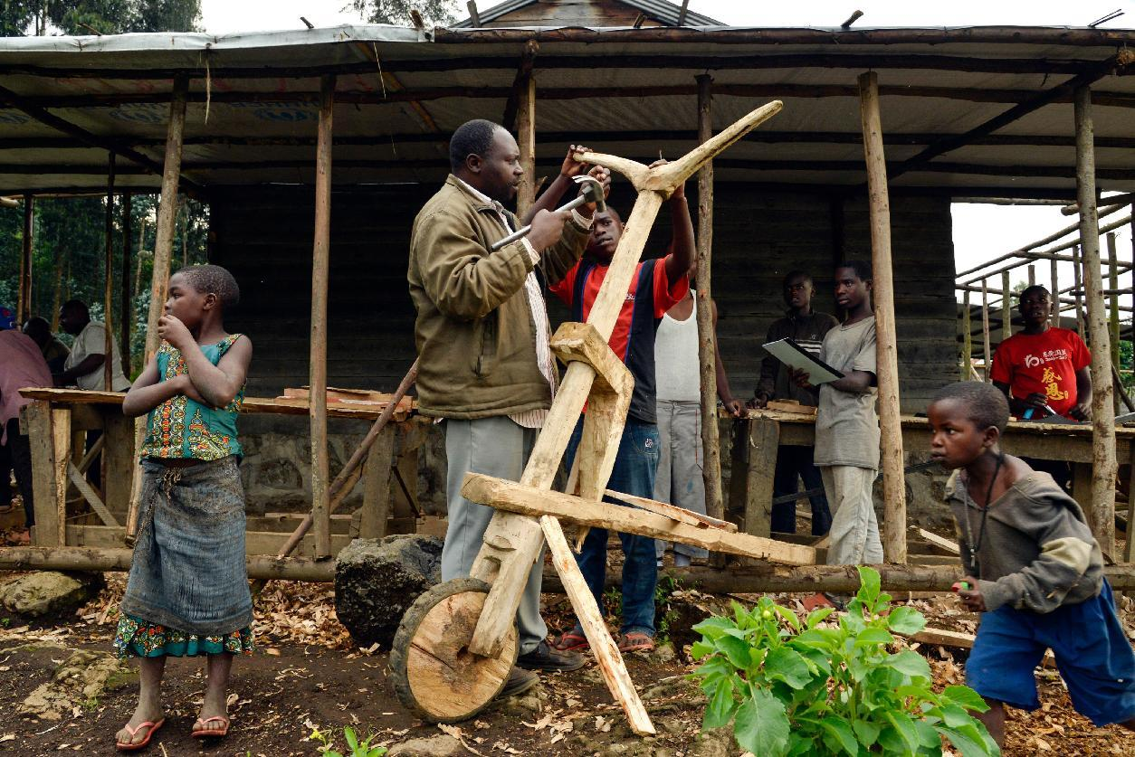 A man makes a tshukudu, a wooden push-bike, in a workshop in Nyirangongo, in the Kibumba region, on June 18, 2014 (AFP Photo/Junior D. Kannah)
