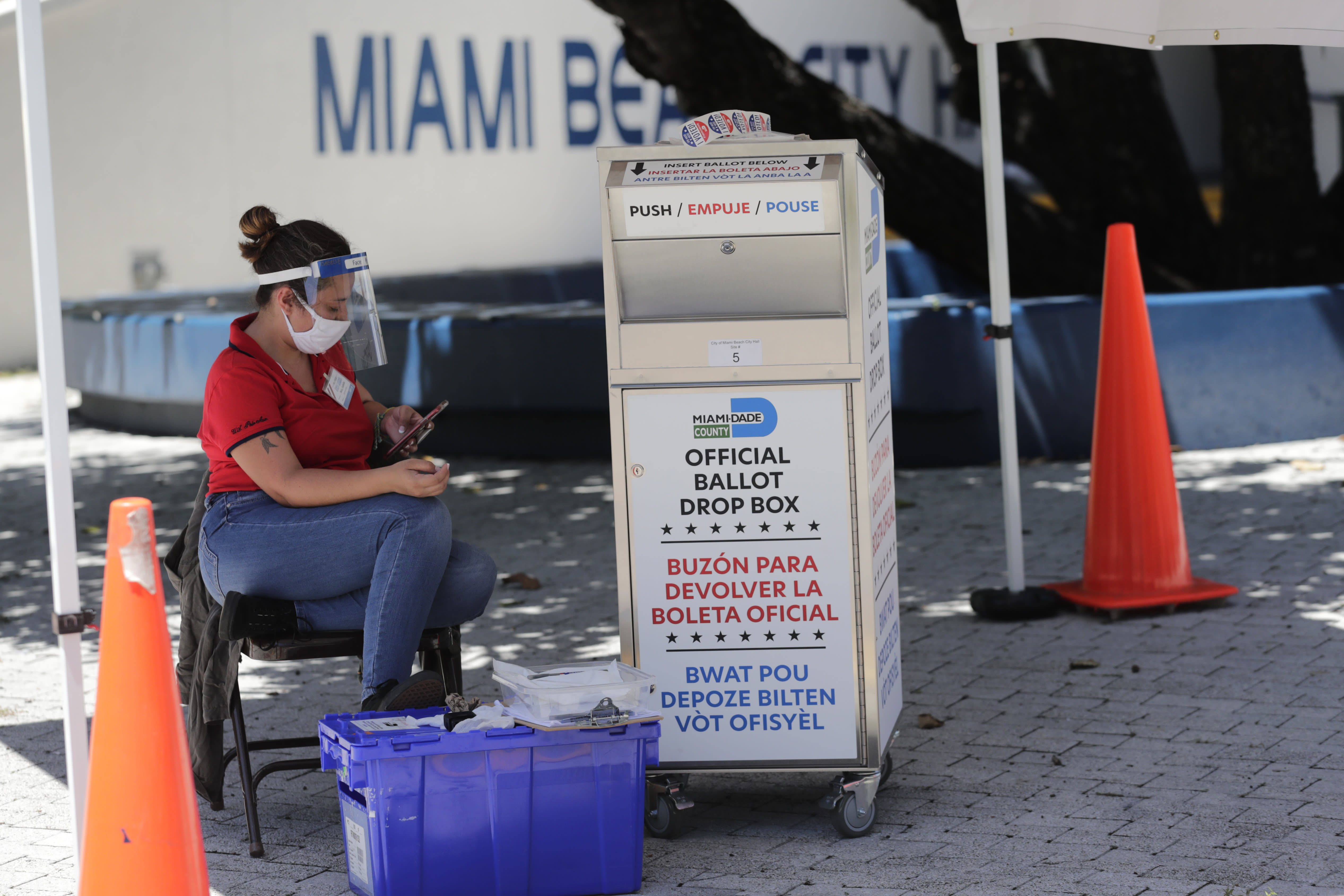 FILE - In this Aug. 7, 2020, file photo, a poll worker wears personal protective equipment as she monitors a ballot drop box for mail-in ballots outside of a polling station during early voting in Miami Beach, Fla. With the Trump administration openly trying to undermine mail-in voting this fall, some election officials around the country are hoping to bypass the Postal Service by installing lots of ballot drop boxes in libraries, community centers and other public places. (AP Photo/Lynne Sladky, File)