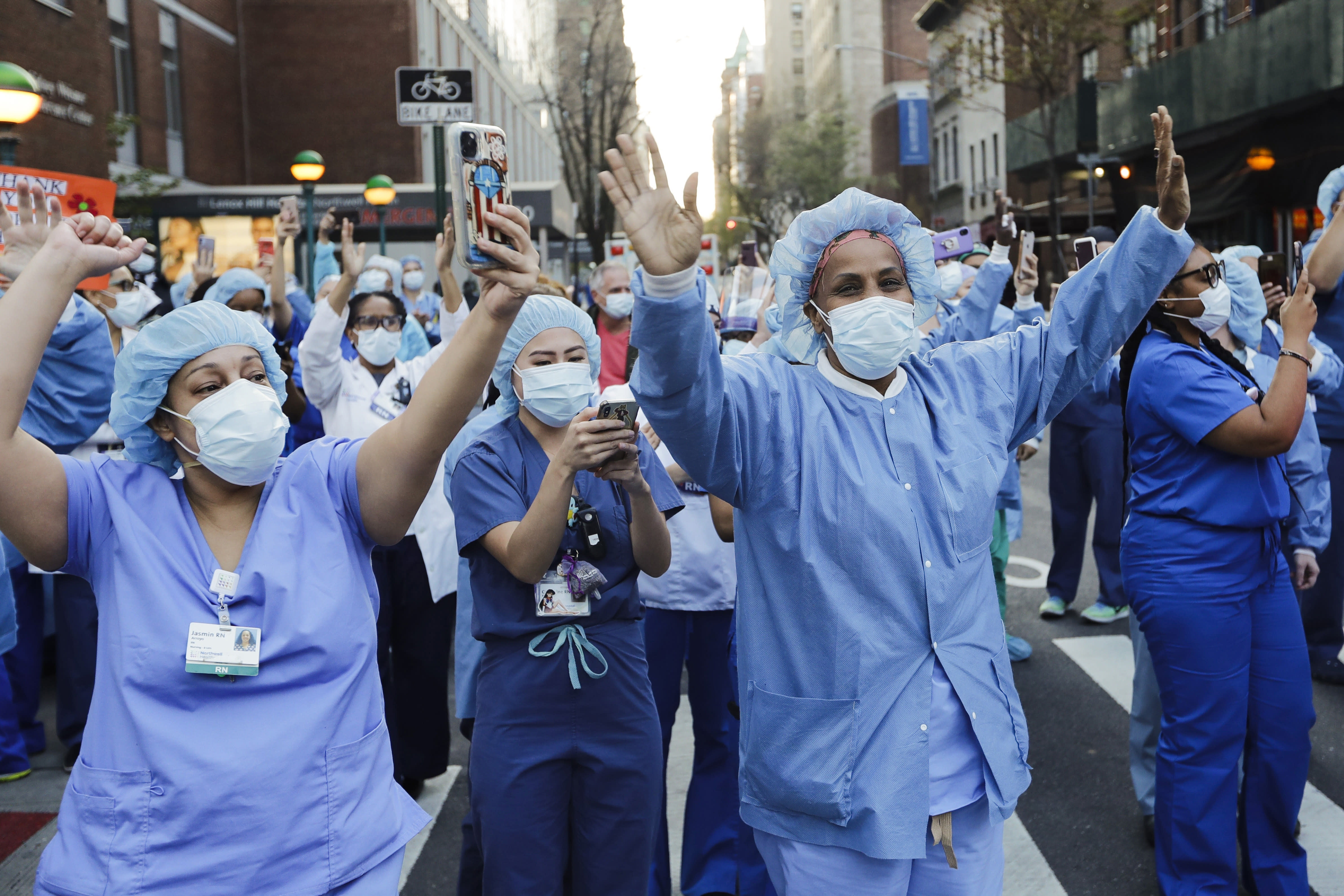 FILE- In this April 15, 2020 file photo, nurses and medical workers react as police officers and pedestrians cheer them outside Lenox Hill Hospital in New York. Nurses on the front lines of New York's COVID-19 pandemic are calling for the state to enact minimum staffing standards ahead of another wave of infections.(AP Photo/Frank Franklin II)