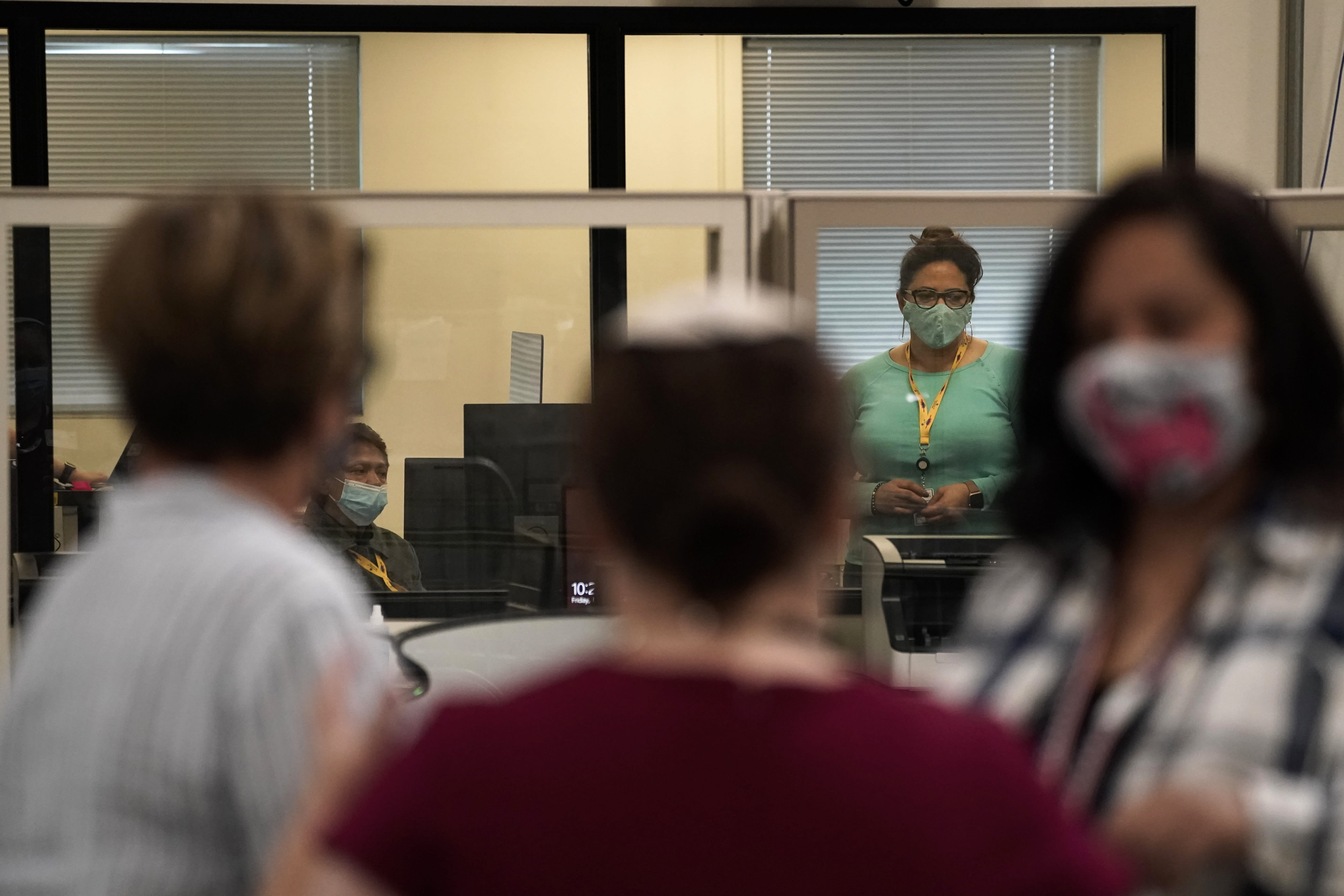 Observers, in foreground, chat as election workers work in a tabulation room at the Clark County Election Department in North Las Vegas, Friday, Nov. 6, 2020. (AP Photo/Jae C. Hong)