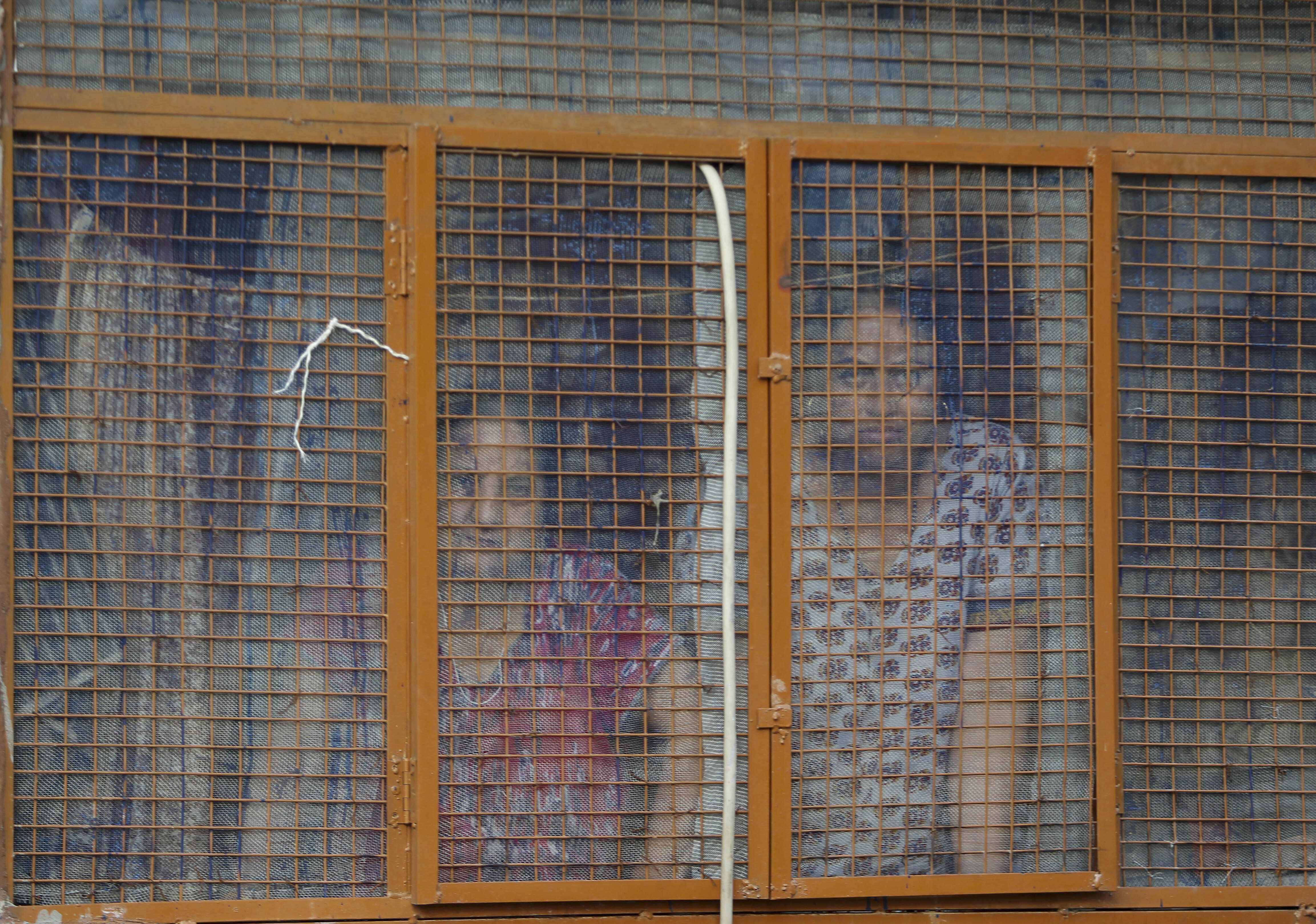 In this Aug. 23, 2019, photo, Kashmiri Hindu women look from inside their residence at the Jagti migrant camp in Jammu, India. Tens of thousands of Kashmiri Hindus fled the restive region nearly 30 years ago, and the ghost of insurgency and their mass exodus still haunts them. They celebrated after India's Hindu nationalist-led government stripped political autonomy from its part of Muslim-majority Kashmir on Aug. 5. Kashmiri Hindus view it as a step toward justice and possible return to their homeland. But many are still wary of returning. (AP Photo/Channi Anand)