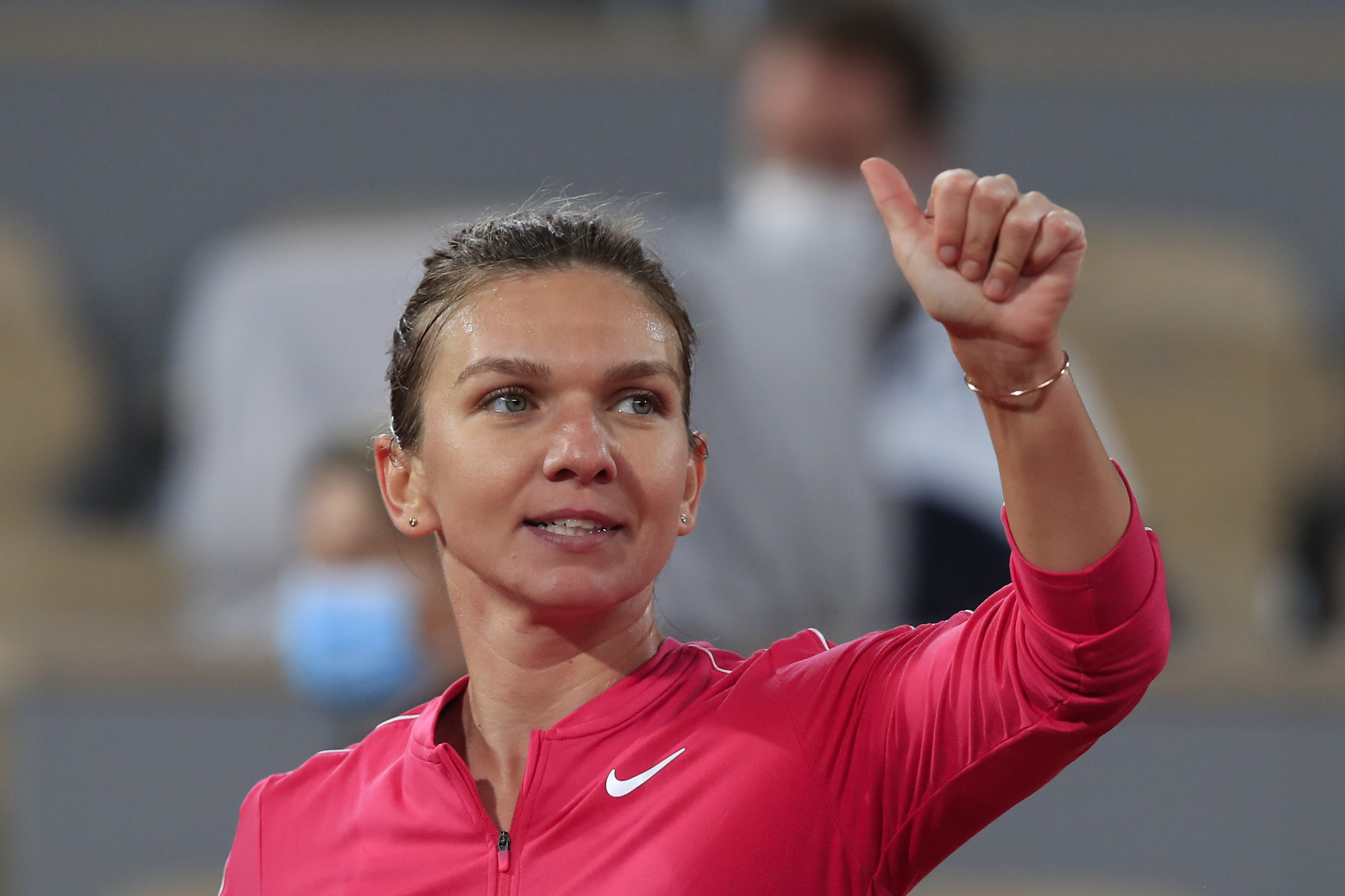 Romania's Simona Halep flashes a thumbs up after winning her third round match of the French Open tennis tournament against Amanda Anisimova of the U.S. in two sets, 6-0, 6-1, at the Roland Garros stadium in Paris, France, Friday, Oct. 2, 2020. (AP Photo/Michel Euler)