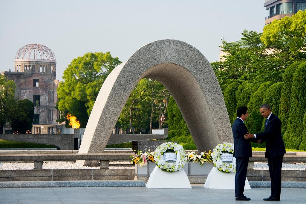 US President Barack Obama (R) and Japanese Prime Minister Shinzo Abe shake hands after laying wreaths at the Hiroshima Peace Memorial Park on May 27, 2016 (AFP Photo/Jim Watson)
