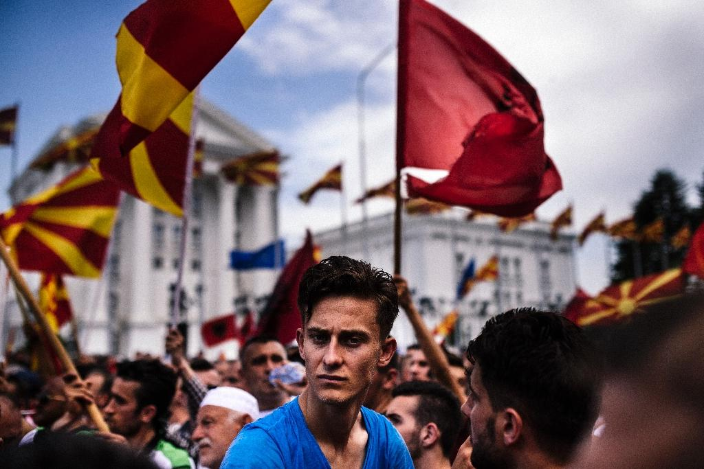 A man looks on as people wave Macedonian and Albanian flags during an anti-government protest in downtown Skopje on May 17, 2015 (AFP Photo/Dimitar Dilkoff)