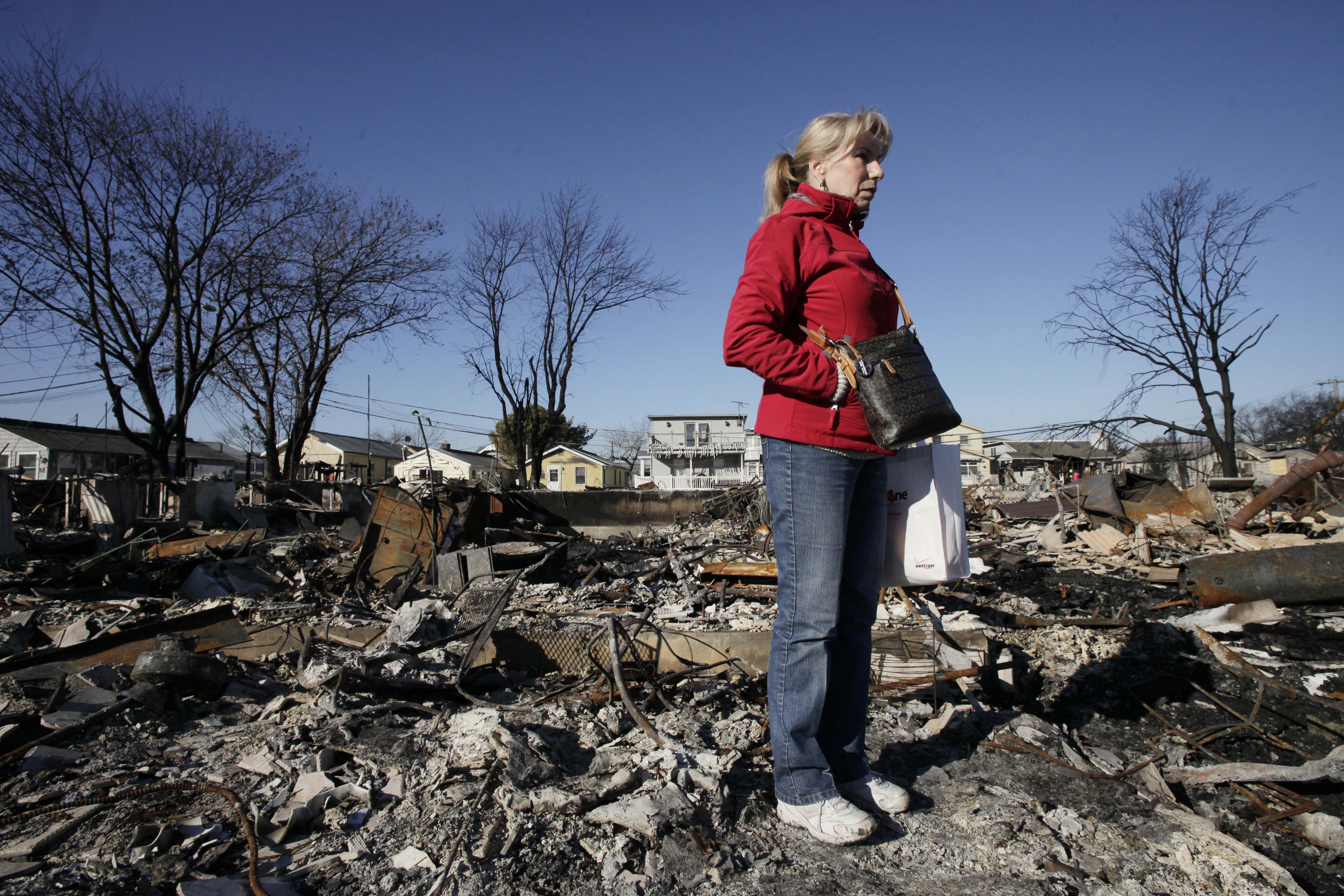 Cathy O'Hanlon poses in front of the charred remains of her home in the Breezy Point section of the Queens borough of New York, Wednesday, Nov. 14, 2012. A fire destroyed more than 50 homes in the oceanfront community during Superstorm Sandy. O'Hanlon and her husband plan to rebuild the house. (AP Photo/Mark Lennihan)