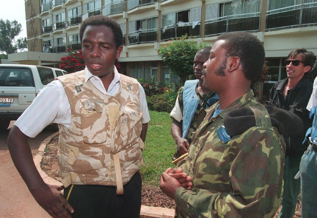 Roman Catholic priest Wenceslas Munyeshyaka (L) speaking with an unidentified Rwandan soldier in Kigali on June 28, 1994