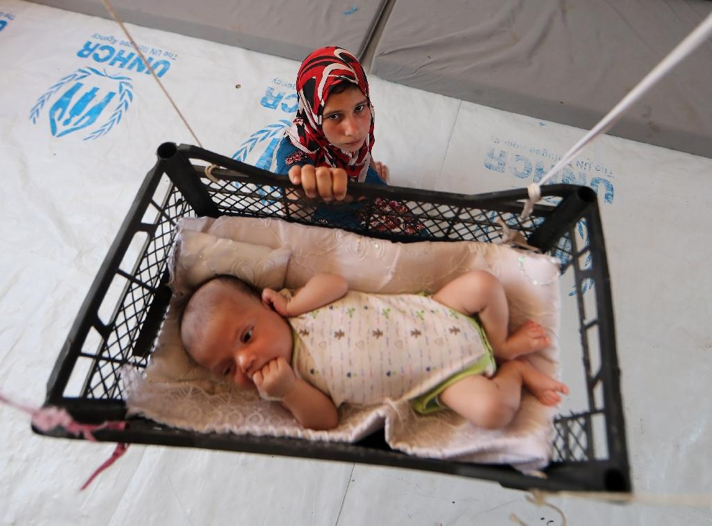 A picture from June 5, 2017 shows a displaced Iraqi girl swinging her baby brother in a makeshift hanging crib in their tent at Khazir camp between Arbil and Mosul (AFP Photo/KARIM SAHIB)