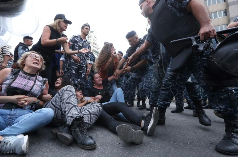 Lebanese security forces remove protesters blocking a major bridge in the centre of the capital Beirut during an anti-government protest (AFP Photo/STR)