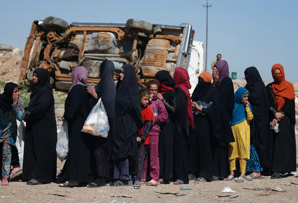 Women and children who fled fighting in Mosul wait to receive food in the western part of the city on April 6, 2017 (AFP Photo/AHMAD GHARABLI)