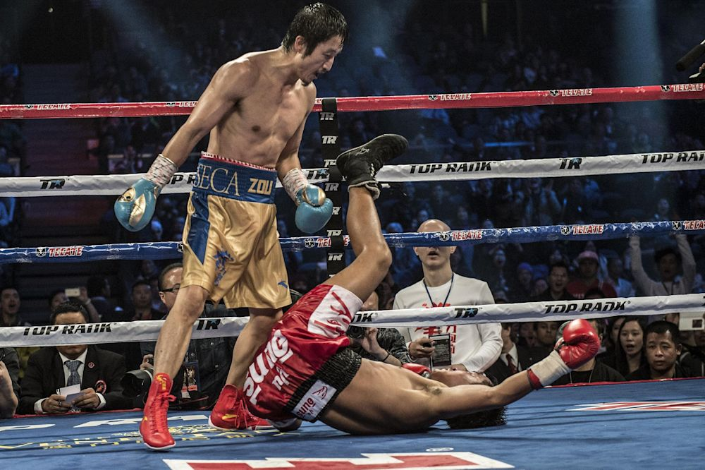 Zou Shiming (L) of China stands over Yokthong Kokietgym of Thailand after a knock out punch to win their flyweight bout in Macau on February 22, 2014