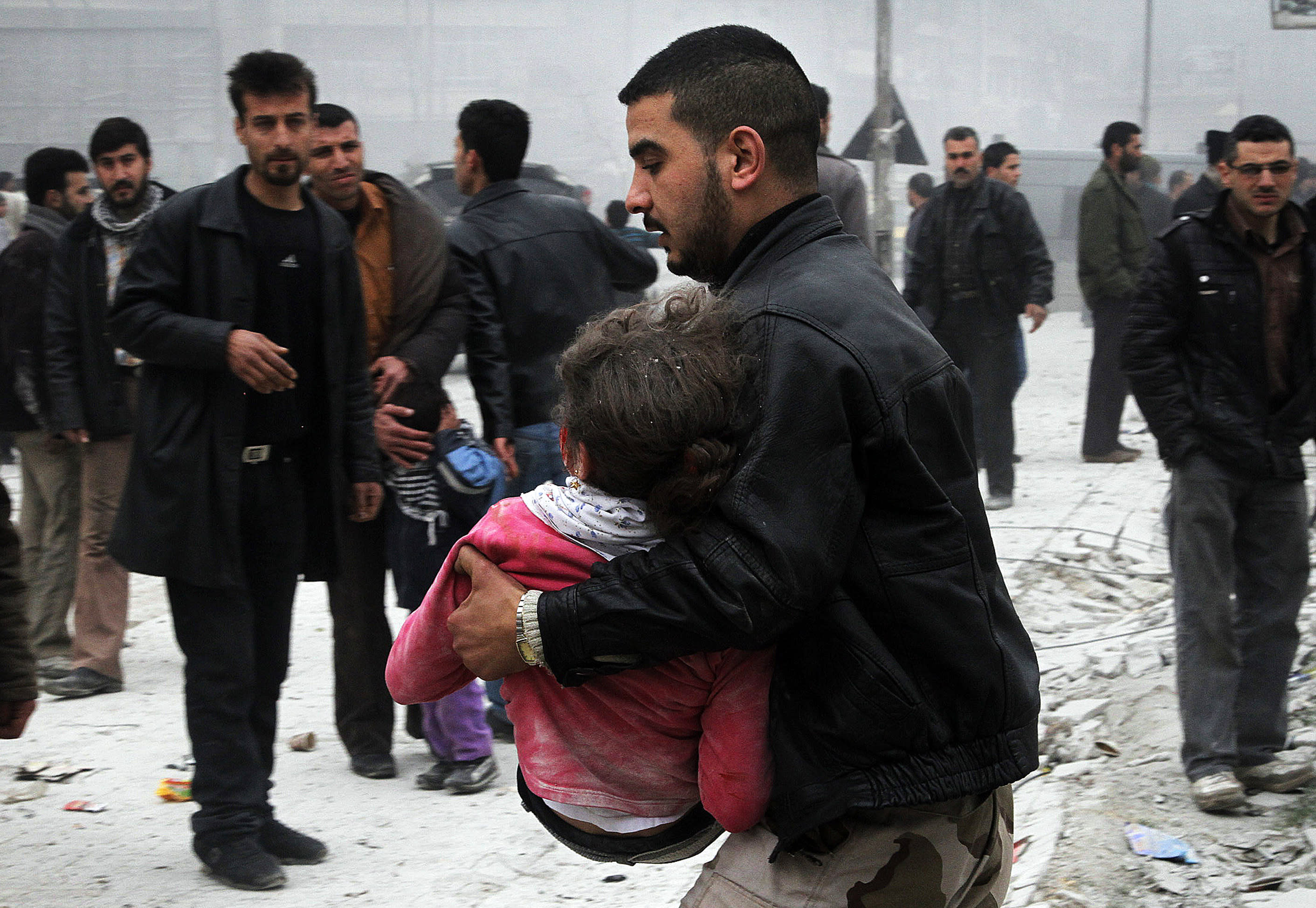 Syrian man carries his relative who was wounded by a government airstrike hit the neighborhood of Ansari, in Aleppo, Syria, Sunday, Feb. 3, 2013. The Britain-based activist group Syrian Observatory for Human Rights, which opposes the regime, said government troops bombarded a building in Aleppo's rebel-held neighborhood of Eastern Ansari that killed over 10 people, including at least five children. (AP Photo/Abdullah al-Yassin)