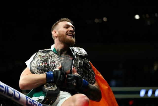 Conor McGregor celebrates with his two title belts after winning at UFC 205. (Getty)