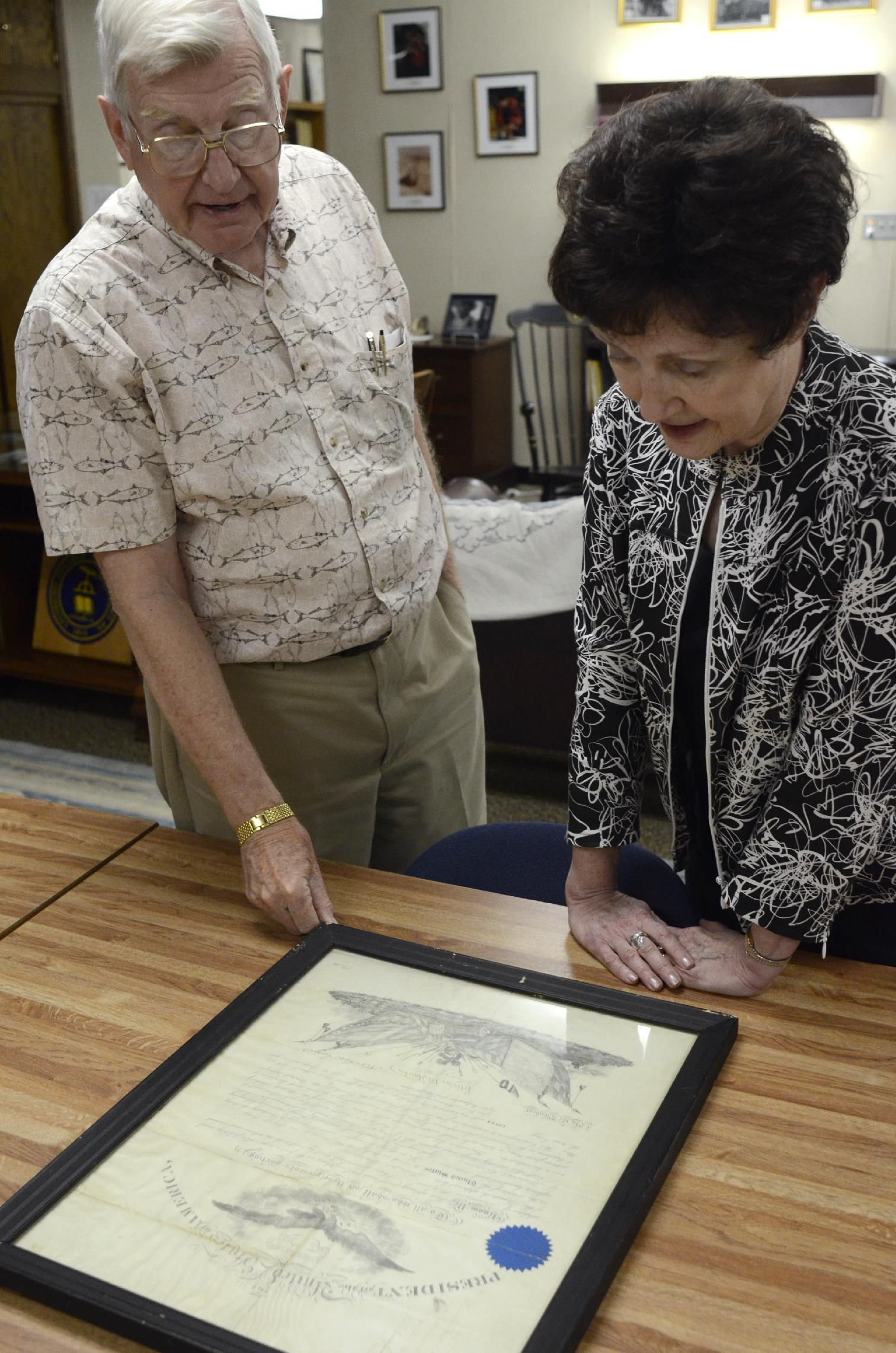 In this Tuesday, June 4, 2013, photo, Lycoming College historian, John Piper, left, and Janet Hurlbert, dean and director of the Snowden Library, look over a certificate signed by Abraham Lincoln in the college archives in Williamsport, Pa. The document naming the school's founder as a Civil War chaplain resurfaced after going missing years ago. (AP Photo/Ralph Wilson)