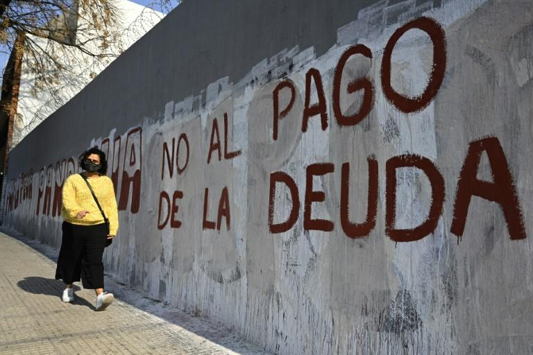 "A woman passes by a wall reading ""No to the debt payment"" in Buenos Aires, on August 3, 2020 -- the day before a deal was reached on restructuring of $66 billion of debt"