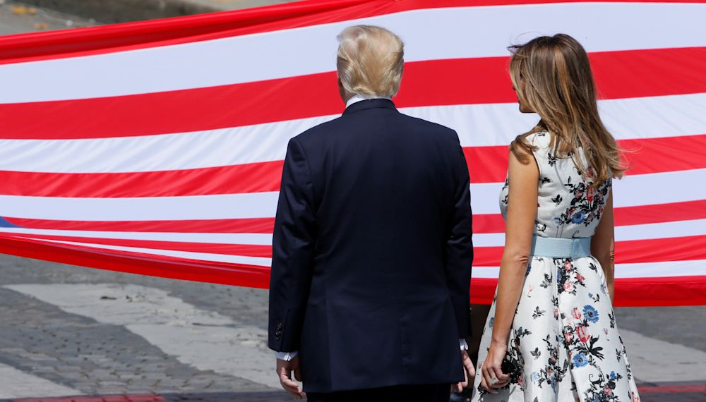 President Donald Trump and Melania Trump stand in front of the American flag