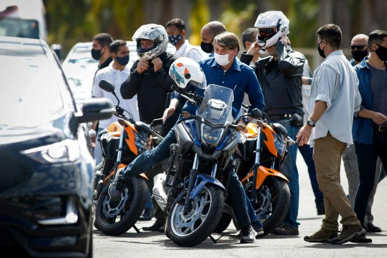 Brazilian President Jair Bolsonaro rode his motorcycle through Brasilia and visited some shops, with small crowds gathering around him (AFP Photo/Sergio LIMA)