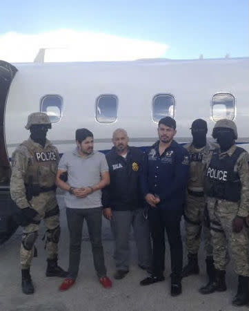 Handout photo of Efrain Antonio Campo Flores and Franqui Fancisco Flores de Freitas stand with Haitian law enforcement officers in this November 12, 2015 photo after their arrest in Port Au Prince, Haiti.