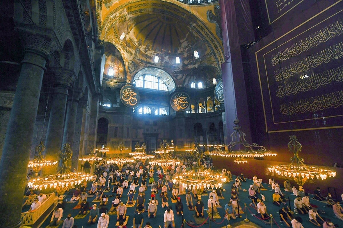 Muslims, wearing protective masks as a precaution against infection from coronavirus gather for the Eid al-Adha prayer inside the Byzantine-era Hagia Sophia, recently converted back to a mosque, in the historic Sultanahmet district of Istanbul, Friday, July 31, 2020. Muslims worldwide marked the the Eid al-Adha holiday over the past days amid a global pandemic that has impacted nearly every aspect of this year's celebrations. (Pool via AP)