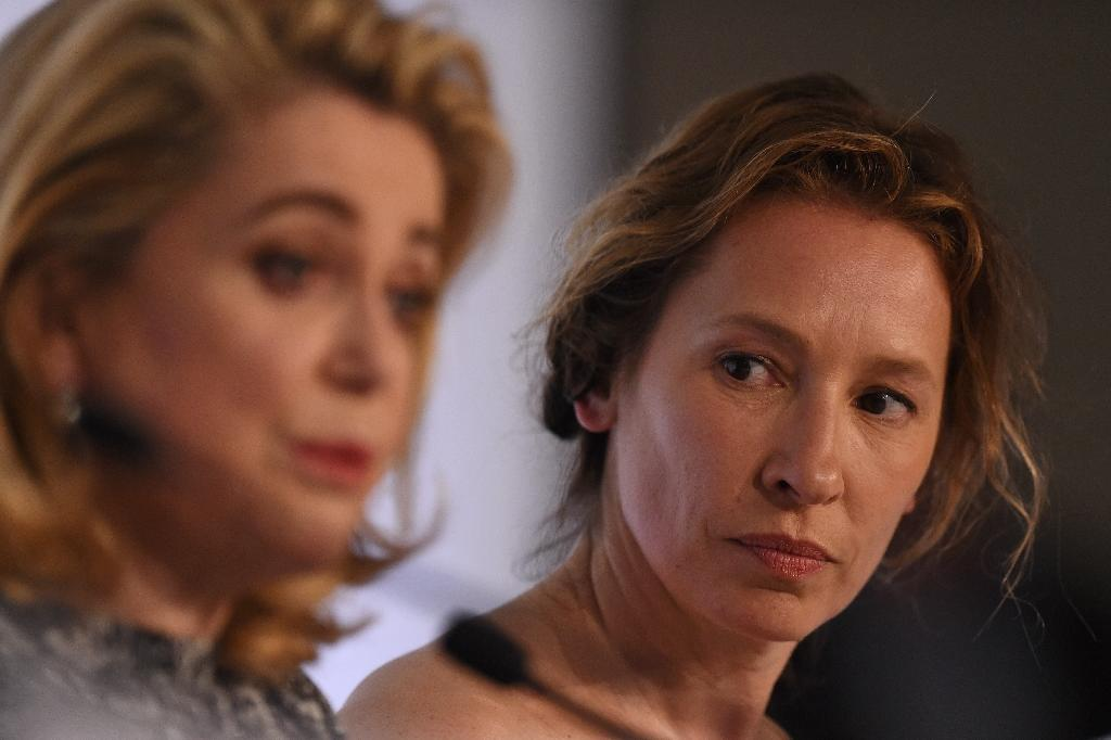"""French director Emmanuelle Bercot (R) looks at actress Catherine Deneuve during a press conference for """"Standing Tall"""" at Cannes Film Festival on May 13, 2015 (AFP Photo/Anne-Christine Poujoulat)"""