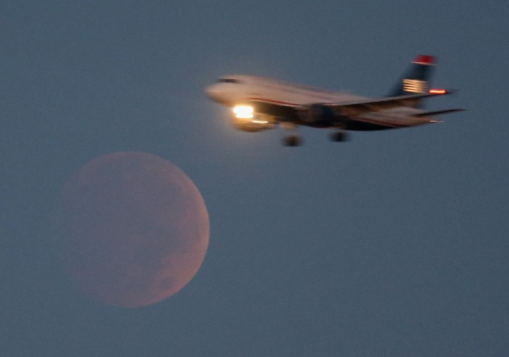 A commercial airliner approaches Reagan National Airport in Washington, DC, as it flies past the full moon during a lunar eclipse on October 8, 2014 (AFP Photo/Mark Wilson)