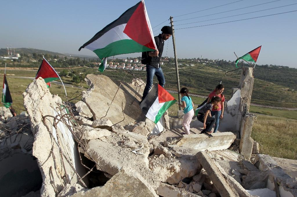 Palestinians from the West Bank village of Nabi Saleh wave their national flag as they stand on a house after it was demolished by Israeli bulldozers under the pretext that there was no construction permit (AFP Photo/Abbas Momani)
