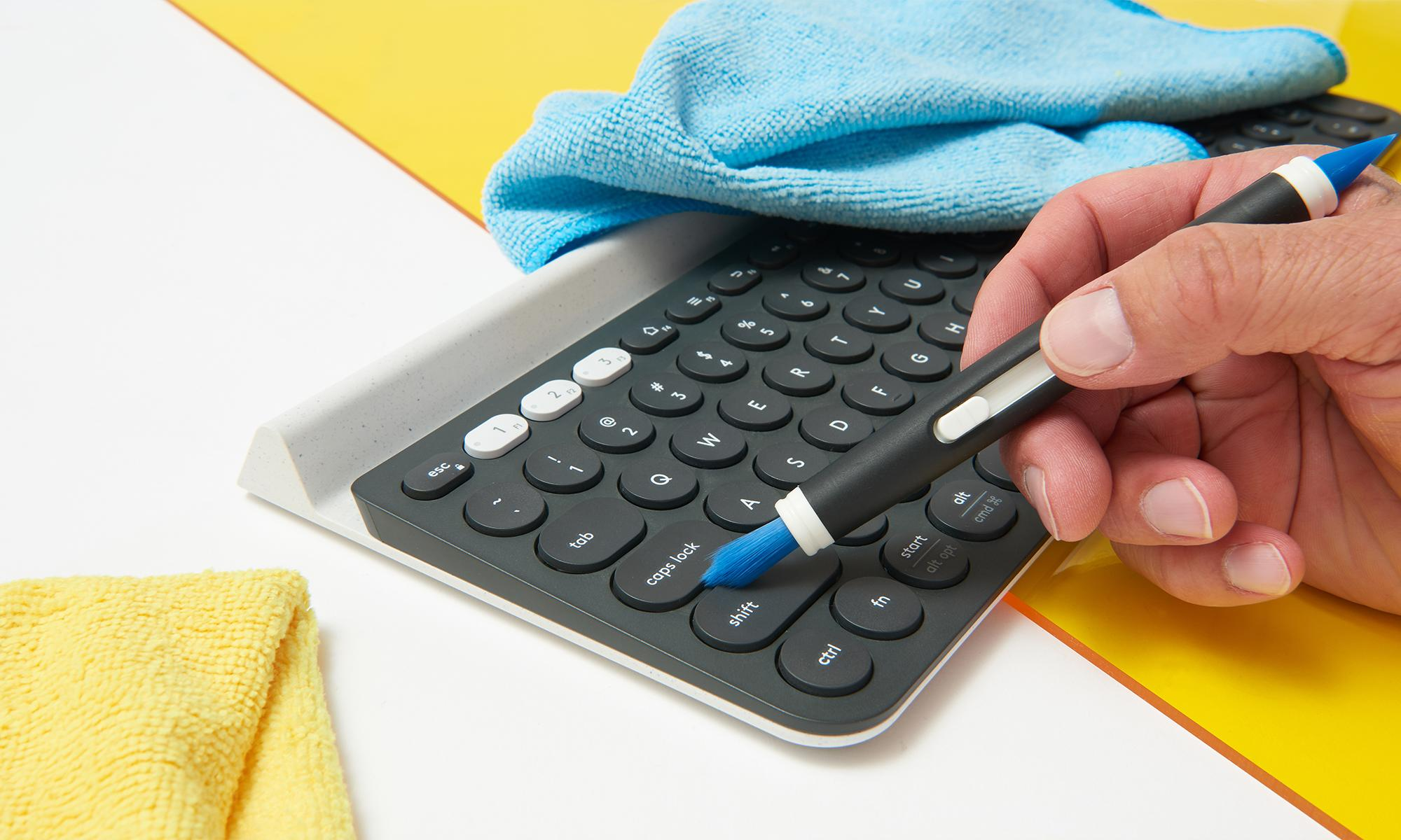 A wireless keyboard is being cleaned by a brush with clothes scatter in the background.