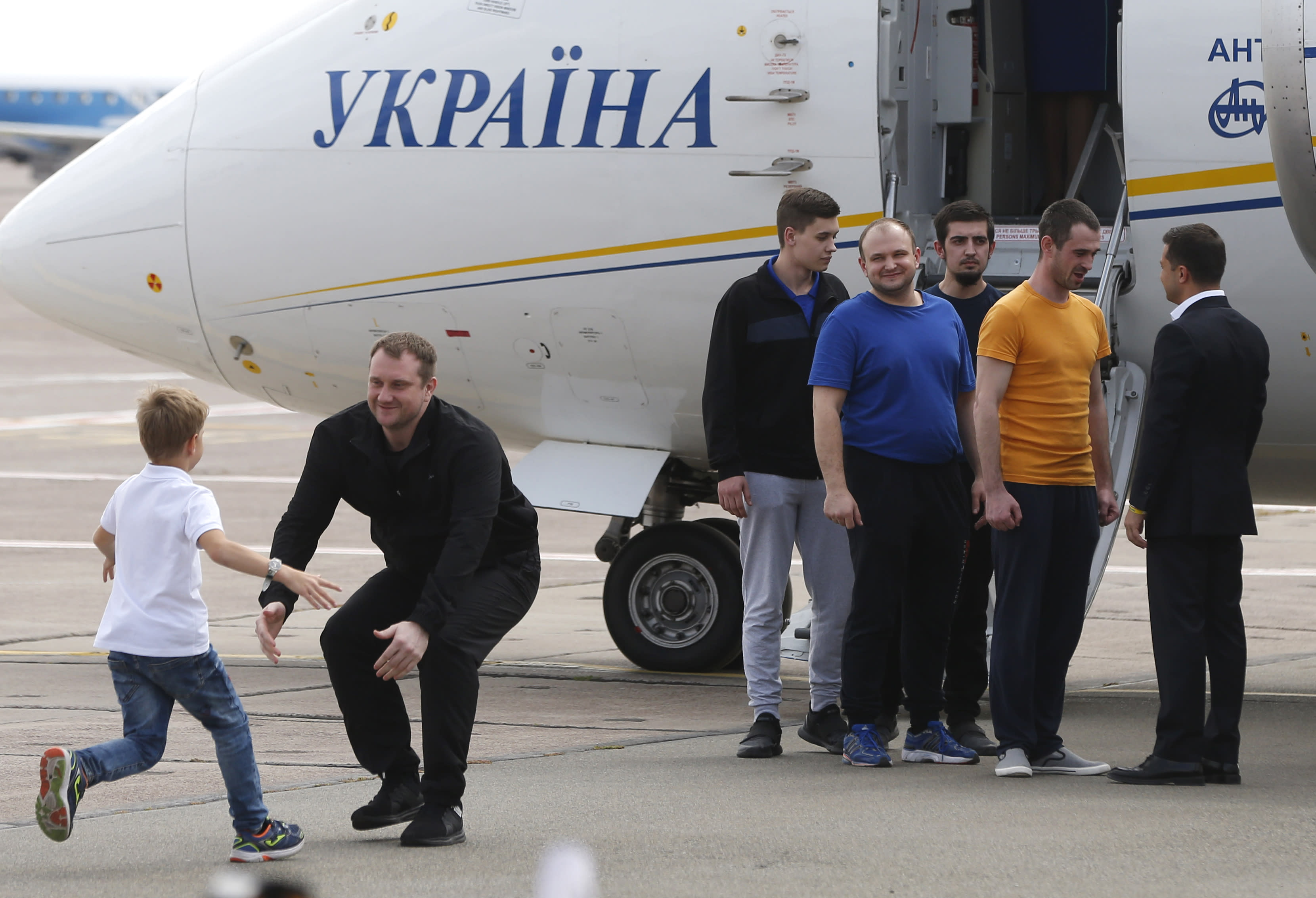 Ukraine's President Volodymyr Zelenskiy, right, greets Ukrainian prisoners upon their arrival at Boryspil airport, outside Kyiv, Ukraine, Saturday, Sept. 7, 2019. Planes carrying prisoners freed by Russia and Ukraine have landed in the countries' capitals, in an exchange that could be a significant step toward improving relations between Moscow and Kyiv. The planes, each reportedly carrying 35 prisoners, landed almost simultaneously at Vnukovo airport in Moscow and at Kyiv's Boryspil airport. (AP Photo/Efrem Lukatsky)