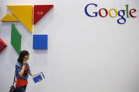 File photo of a woman walking past a logo of Google at the Global Mobile Internet Conference (GMIC) 2015 in Beijing