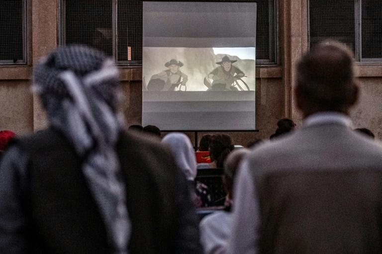 Not having been to the cinema in decades, even some of the older men in the village come to see the cartoon being screened (AFP Photo/DELIL SOULEIMAN)